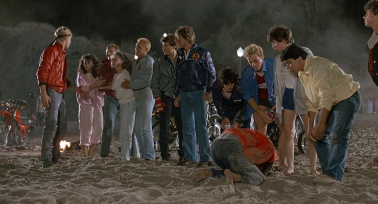 Cobra Kai students bullying Daniel and Ali at the beach.